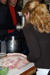 Charcuterière Julie Biggs begins to prepare pork by slicing it into cubed pieces.